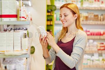 Frau haelt Produkt in der Drogerie in der Hand