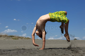 Bolsena  Italien  ein Junge macht am Strand einen Ueberschlag