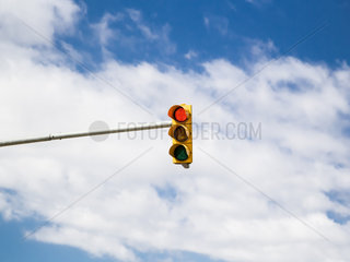 Red traffic light on cloud sky background.