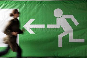Basel  Schweiz  Frau rennt an einem Notausgangsschild vorbei
