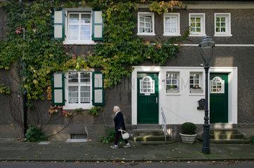 Essen  Deutschland  aeltere Frau vor den Reihenhaeusern in der Gartenstadt Margarethenhoehe