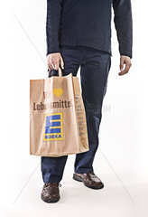 Mann mit Papiertuete von Edeka