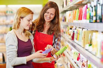 Frau neben Verkaeuferin vergleicht Produkte in Drogerie