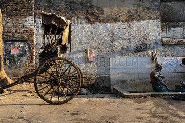 Kolkata  Indien  Asien  Ein Rikschalaeufer duscht am Strassenrand