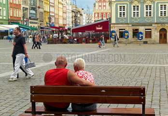 Breslau  Polen  ein Paar sitzt auf einer Holzbank auf dem Marktplatz