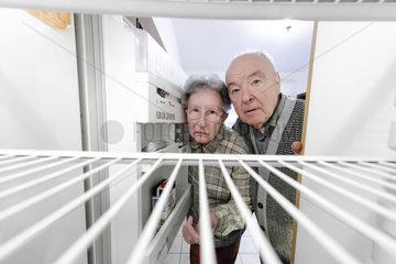 Rentner sehen in leeren Kuehlschrank