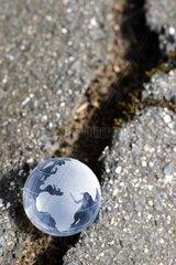 Weltkugel in einer Erdspalte  Umweltzerstoerung
