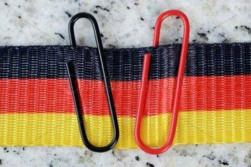 Schwarze und rote Bueroklammer an einer Deutschlandfahne  Symbolfoto Grosse Koalition