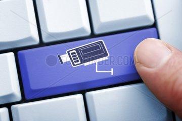 Finger auf Computertaste mit Kamerasymbol  Onlineueberwachung