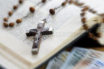Kreuz mit Rosenkranz auf Bibel und Geldscheine  Kirche und Finanzen