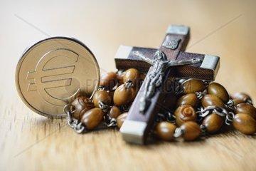 Kreuz mit Rosenkranz und Eurozeichen  Kirche und Finanzen