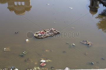 Opfergaben in einem verschmutzten Fluss