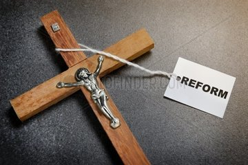 Kreuz mit Etikett und Schriftzug Reform  Symbolfoto Kirchenreform