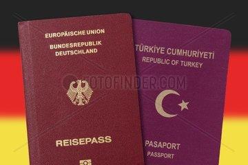 Deutscher und tuerkischer Pass vor Deutschlandfahne  doppelte Staatsbuergerschaft