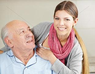 Laechelnde Altenpflegerin mit Senior
