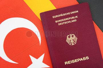 Deutscher Reisepass auf Tuerkei- und Deutschlandfahne  doppelte Staatsbuergerschaft