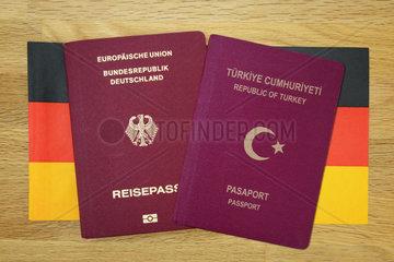 Deutscher und tuerkischer Reisepass auf Deutschlandfahne  doppelte Staatsbuergerschaft
