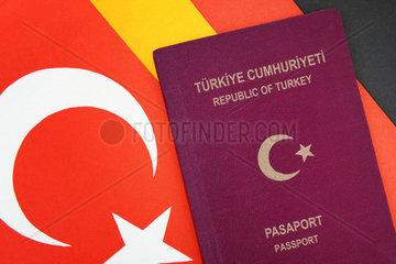Tuerkischer Reisepass auf Tuerkei- und Deutschlandfahne  doppelte Staatsbuergerschaft
