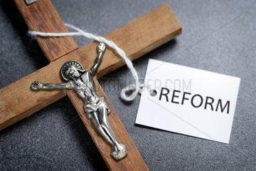Kreuz mit Etikett und Aufschrift Reform  Symbolfoto Kirchenreform