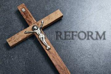 Holzkreuz mit Jesusfigur und Reform-Schriftzug