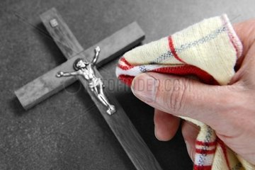 Kreuz und Hand mit Staubtuch  Symbolfoto Kirchenreform