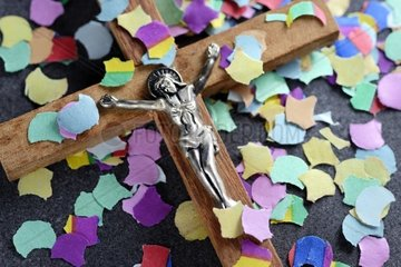 Kreuz mit buntem Konfetti  Symbolfoto Kirchenreform