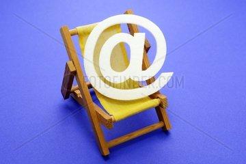At-Zeichen im Liegestuhl  Symbolfoto computerfreier Urlaub