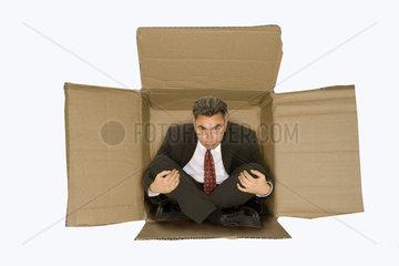 Geschaeftsmann sitzt in Karton