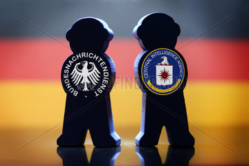 Figuren mit Zeichen von BND und CIA vor deutscher Fahne  Spionage-Skandal