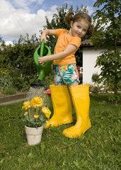 Maedchen giesst ihre gelben Blumen gelben Gummistiefeln