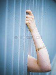 Frauenarm greift zwischen Gitterstaeben hindurch