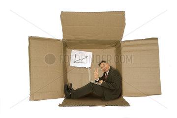 Geschaeftsmann mit Notebook sitzt in der Kiste