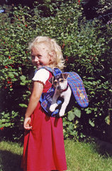 M___dchen mit Jack Russell Terrier im Rucksack