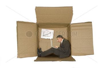 Geschaeftsmann mit Notebook sitzt in der Karton