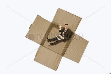 Geschaeftsmann mit Notebook sitzt in Karton