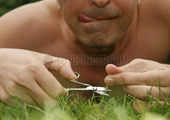 Mann schneidet seinen Rasen mit Nagelschere