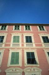 rote Hausfront mit gruenen Laeden