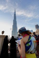 Dubai  Vereinigte Arabische Emirate  Frau schaut am Burj Khalifa auf ihren Tablet-PC