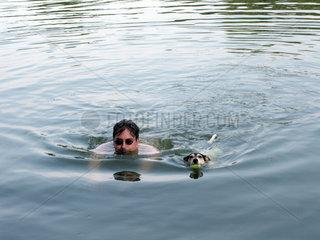 Jack Russell Terrier schwimmt mit Herrchen