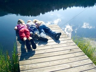Children watch fish at a lake