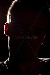 Jugenlicher Straftaeter beim Verhoer oder eine Person die anonym bleiben will bei Interview mit schwarzem Gesicht im Gegenlicht