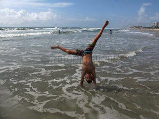 Cape Canaveral  USA  Junge macht am Strand einen Handstand
