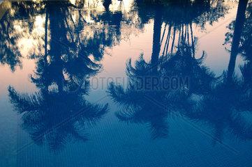 Spiegelung des Sonnenuntergang auf der Wasseroberflaeche eines Hotelpools