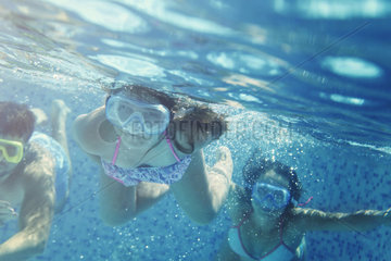 Little girl and friends having fun in pool
