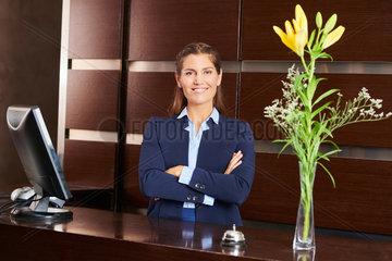 Frau am Empfang im Hotel laechelt freundlich