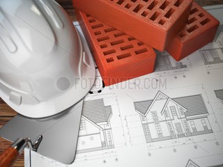 Hard hat  trowel and bricks on the drawings with construction plans. Engineering or construction concept.