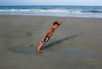 Cocoa Beach  USA  Junge steckt am Strand im Sand fest