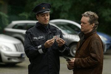 Polizist prueft einen Fuehrerschein