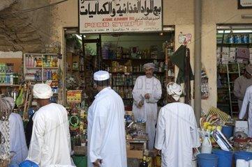 Omanische Maenner an einem Lebensmittelstand auf dem Basar in Nizwa  Sultanat Oman