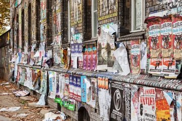 mit Plakaten beschmutzte Hauswand im Berliner Bezirk Friedrichshain